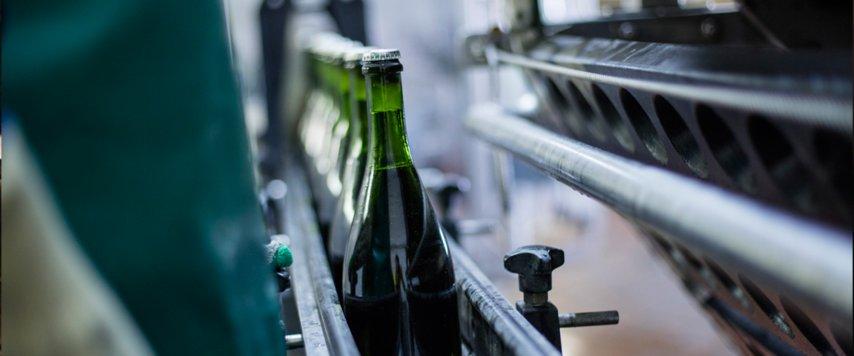 Wine bottles being pressed by machines